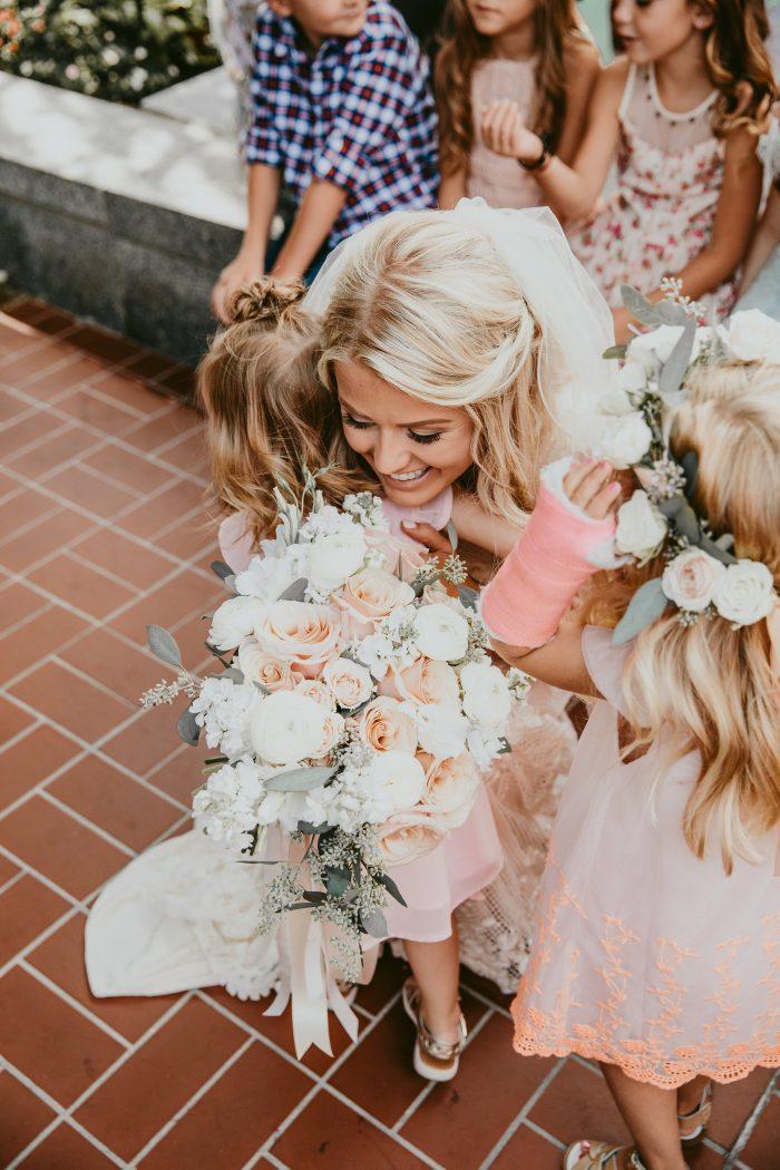Real Bride Wearing Maggie Sottero Wedding Dress Hugging Flower Girls