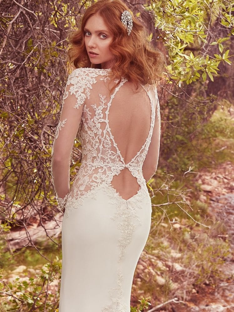 Beautiful statement-back wedding dresses from Maggie Sottero and Sottero and Midgley - A double-keyhole back evokes romance and intrigue, while a godet accented with lace appliqués adds volume to the elegant Yolivia crepe skirt. Blanche by Maggie Sottero.