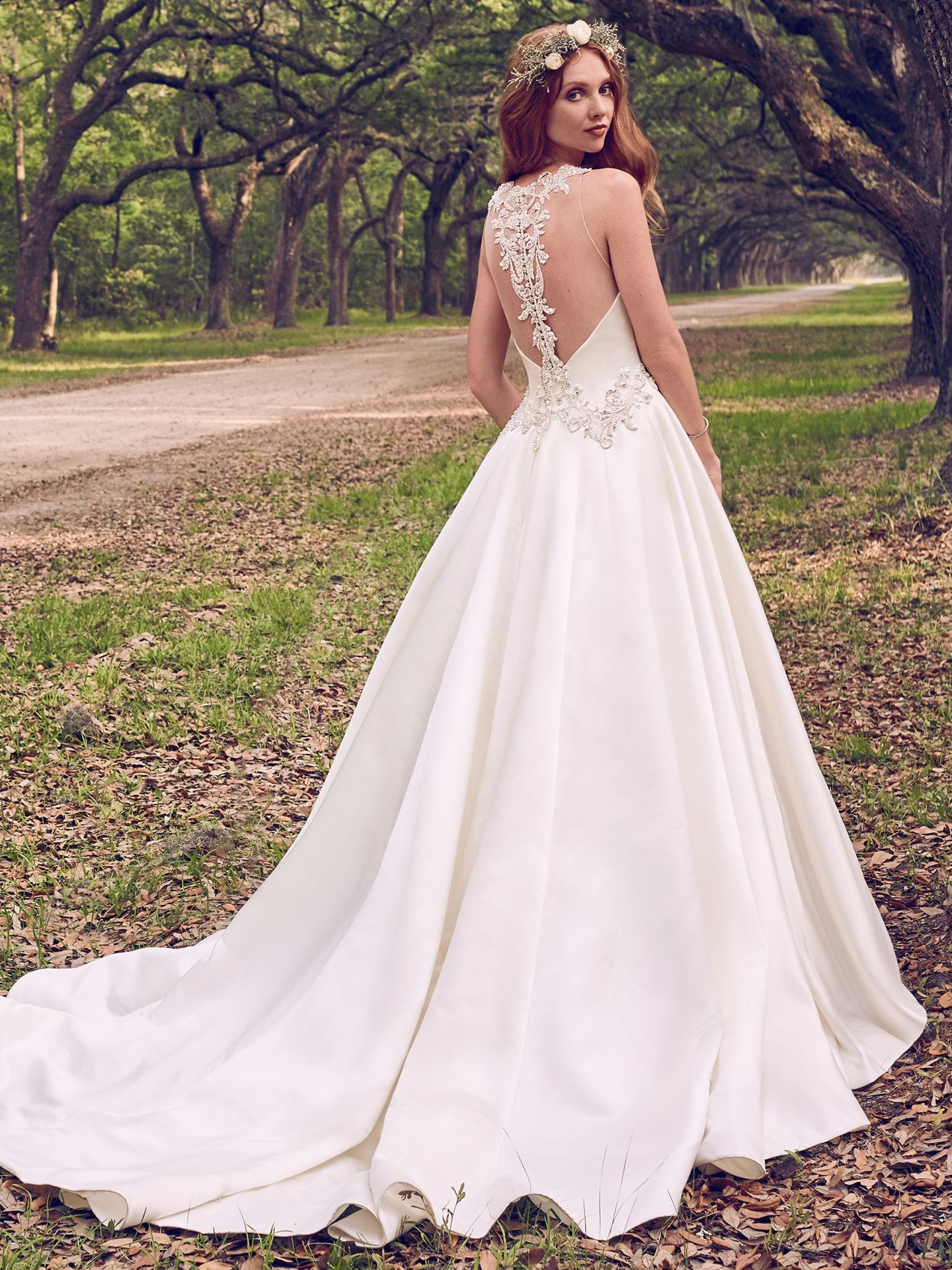 Beautiful statement-back wedding dresses from Maggie Sottero and Sottero and Midgley - Beaded lace motifs and Swarovski crystals adorn the waistline and illusion open back in this Gala Satin wedding dress. Corianne by Maggie Sotter.