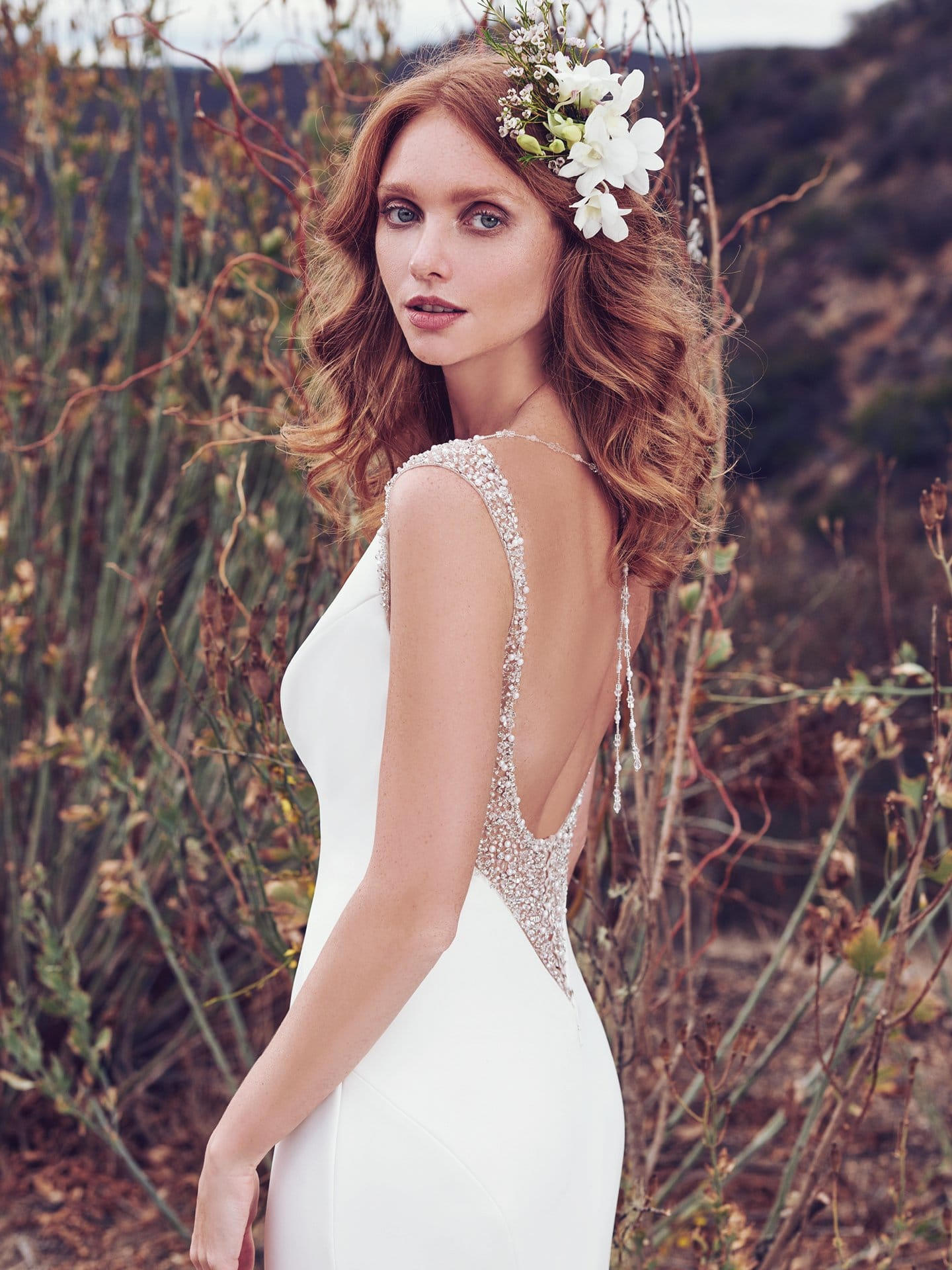 Beautiful statement-back wedding dresses from Maggie Sottero and Sottero and Midgley - Simple yet chic, this Aldora Satin wedding dress features illusion and Swarovski crystals accenting the shoulders, gliding into a shimmering ribbon of pearls and beading that ties in the plunging back, also trimmed in illusion and Swarovski crystals. Evangelina by Maggie Sottero.