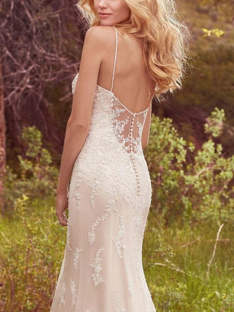 Beautiful statement-back wedding dresses from Maggie Sottero and Sottero and Midgley - Lace appliqués cascade down the bodice, breathtaking scalloped hem, and illusion open-back in this tulle over Vogue satin wedding dress. Nola by Maggie Sottero.
