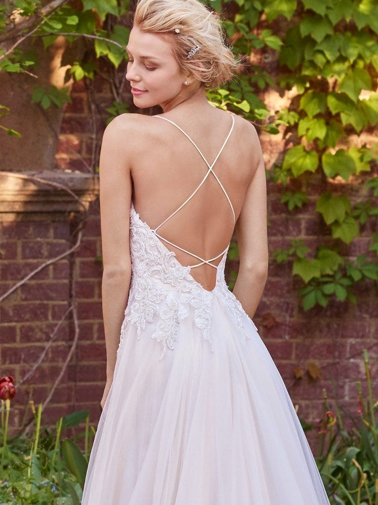 Beautiful statement-back wedding dresses from Maggie Sottero and Sottero and Midgley - SFlirty strap details create a crisscross effect that accents the open plunging back in this tulle A-line wedding dress. Marjorie by Rebecca Ingram.