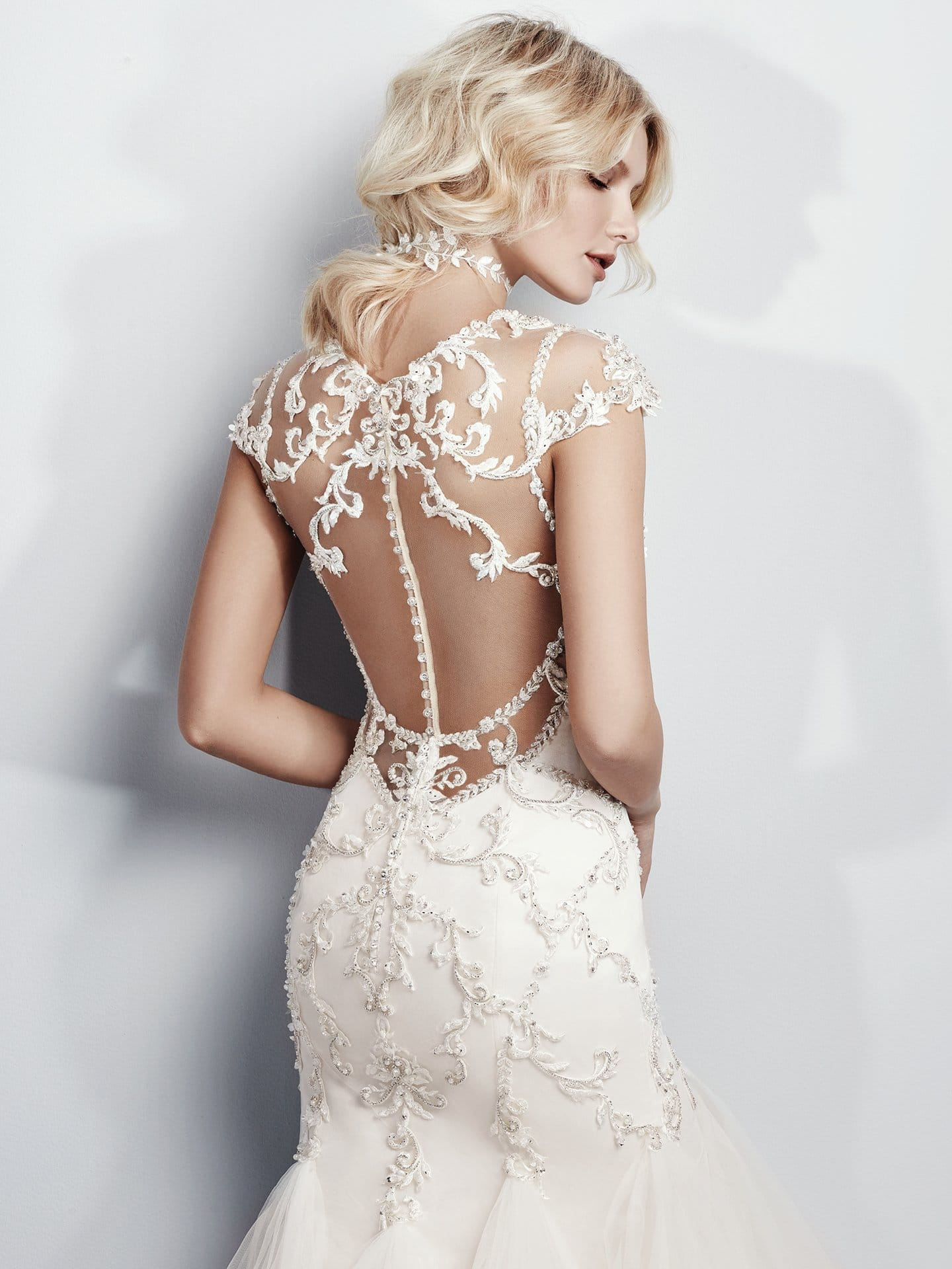 Beautiful statement-back wedding dresses from Maggie Sottero and Sottero and Midgley - This stunning mermaid wedding dress features an illusion sweetheart neckline, cap-sleeves, and open back, all trimmed in beaded lace appliqués and Swarovski crystals. Grayson by Sottero and Midgley.