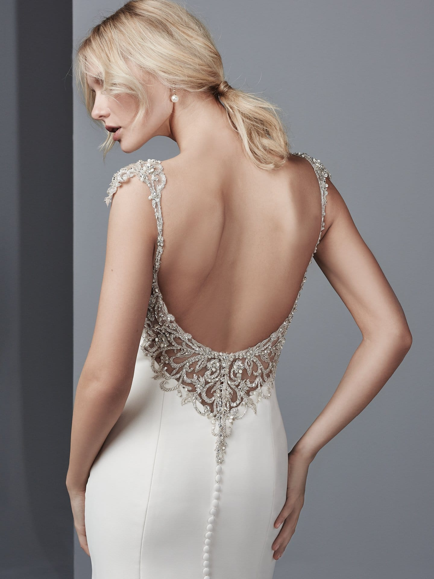 Beautiful statement-back wedding dresses from Maggie Sottero and Sottero and Midgley - Alluring yet sophisticated, this Shavon Organza wedding dress features a bateau neckline, with beaded lace motifs and Swarovski crystals accenting the illusion cap-sleeves and illusion open back. Raquelle by Sottero and Midgley.