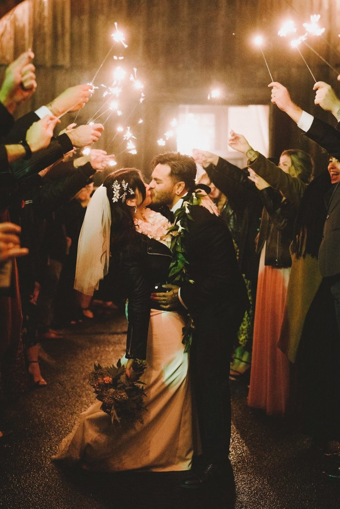 Bride Wearing Beaded Sheath Wedding Dress and Groom Under Sparklers