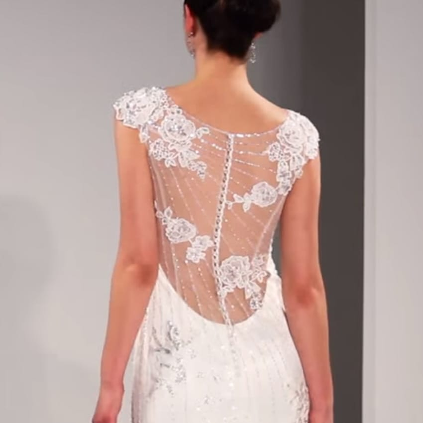 A Model Walking Down the Runway in Backless Wedding Dress by Maggie Sottero