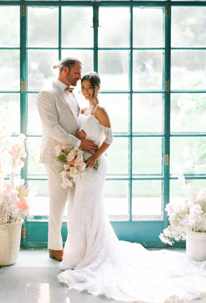 Groom with Bride Wearing Shimmery Boho Wedding Gown Called Conrad by Sottero and Midgley