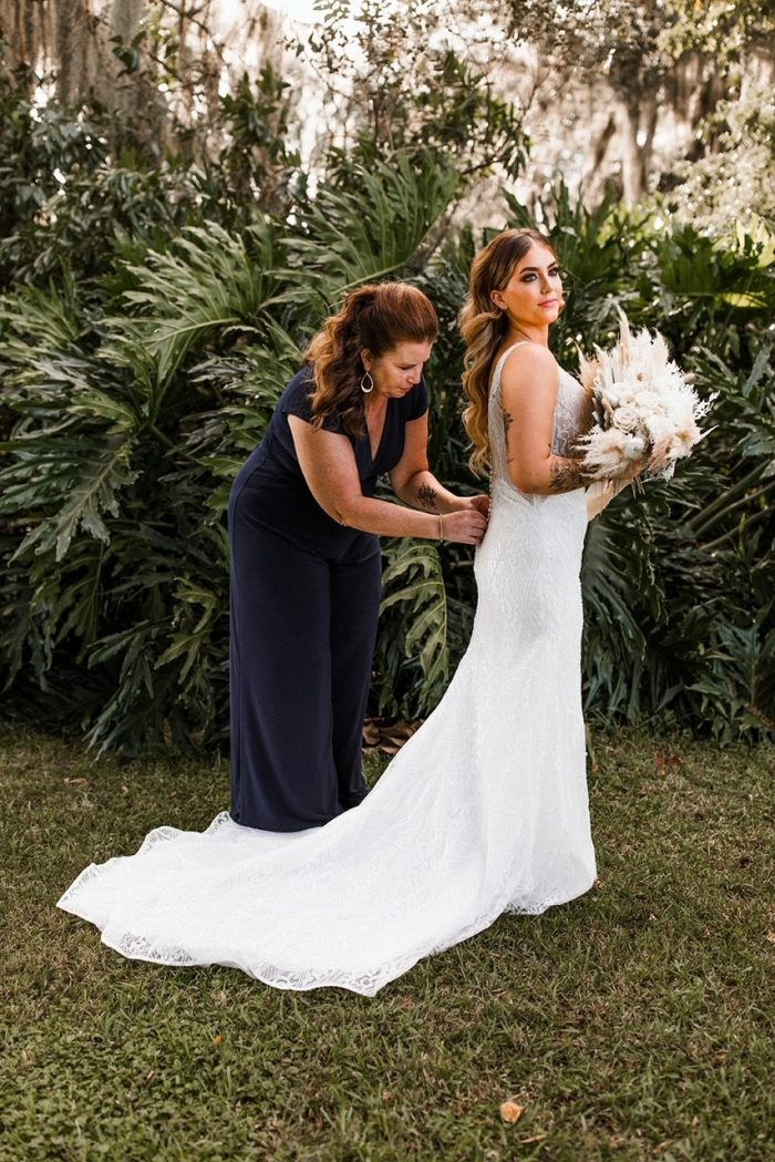 Mother of the Bride Wearing Stylish Jumpsuit While Buttoning Bride's Wedding Dress