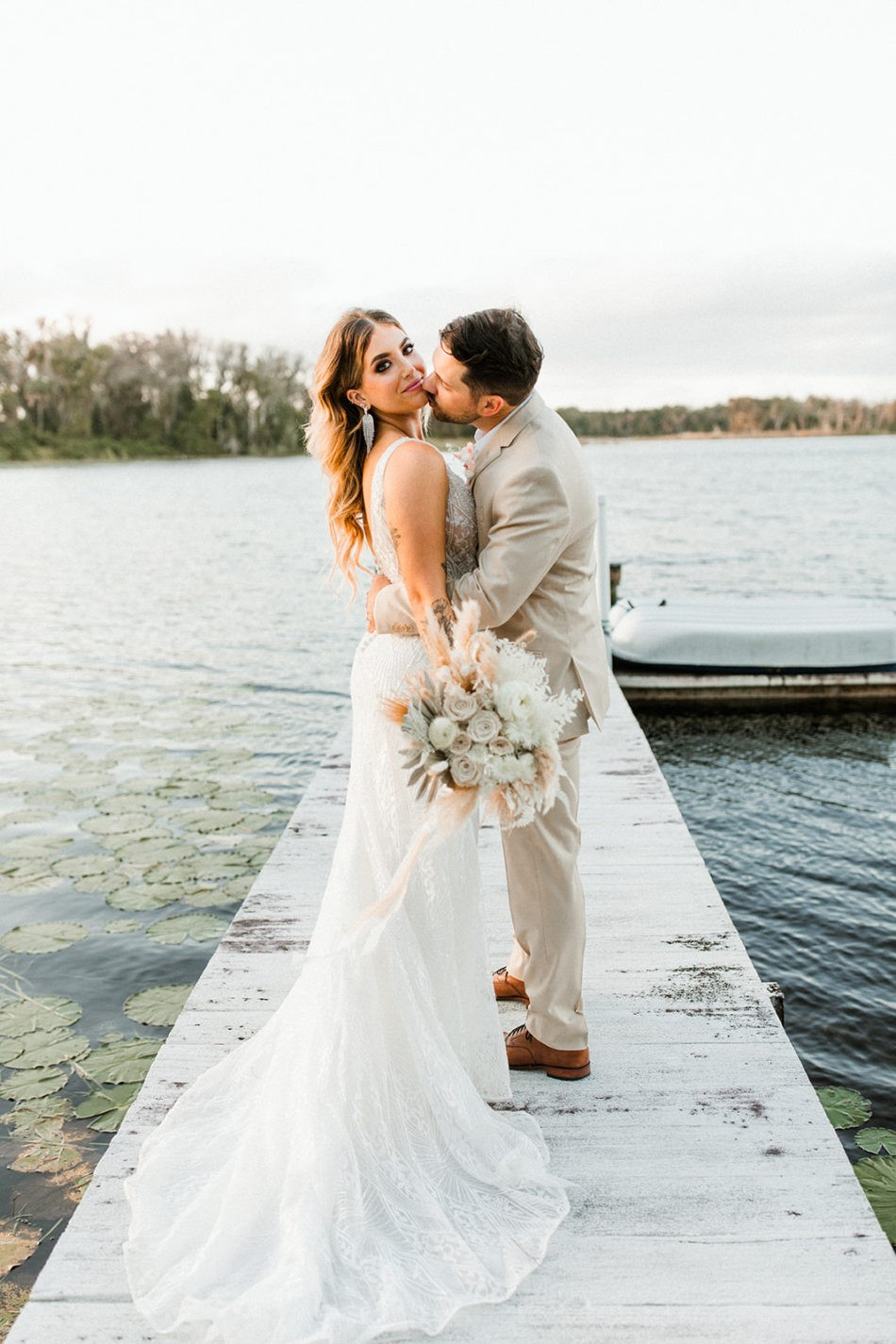 Groom on Dock Kissing Real Bride Wearing Art Deco Wedding Gown called Elaine by Maggie Sottero