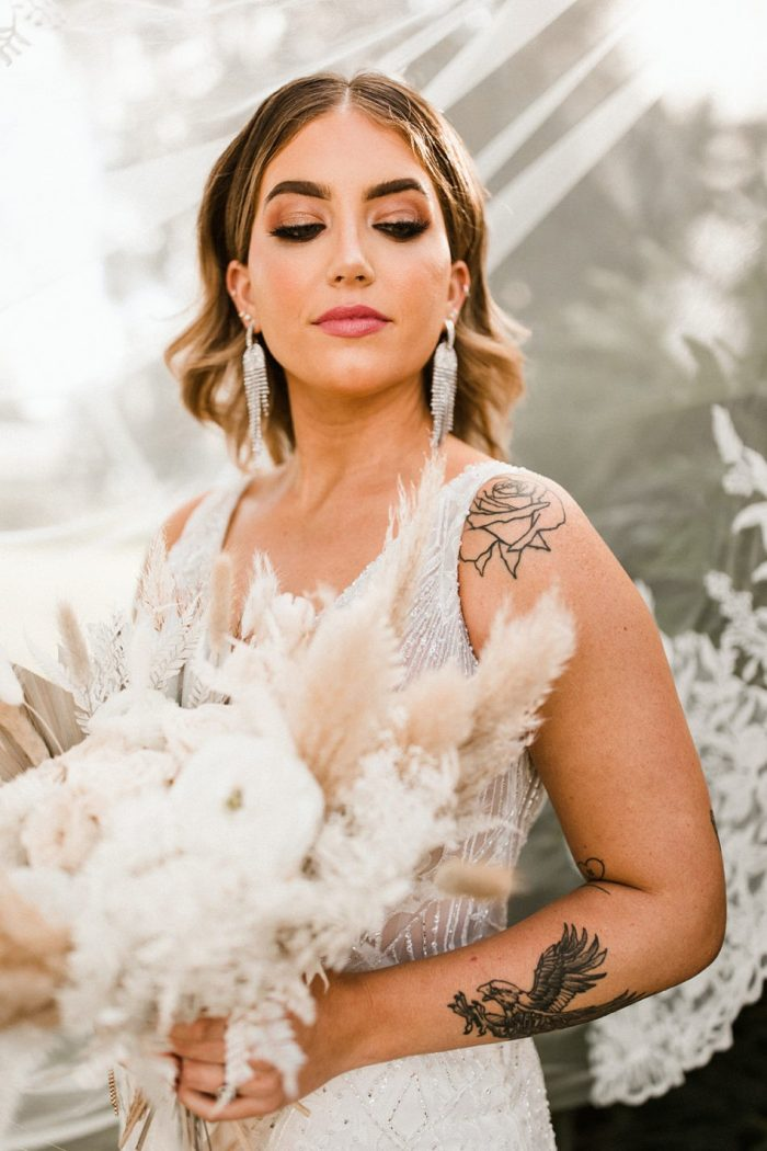 Real Bride Wearing Maggie Sottero Wedding Dress and Holding Modern White Wedding Bouquet