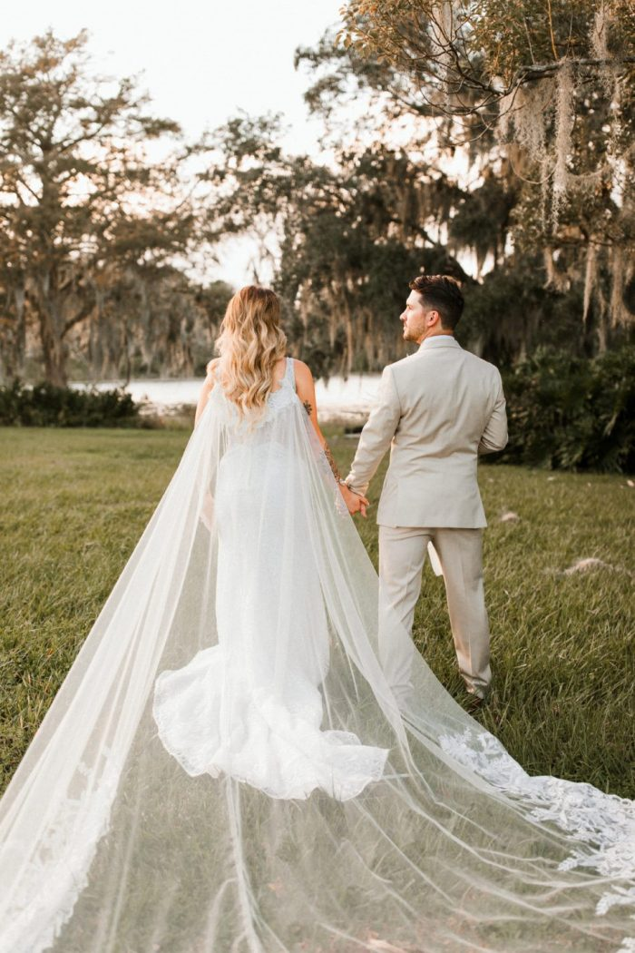 Groom Walking with Real Bride Wearing Bridal Cape and Maggie Sottero Wedding Dress