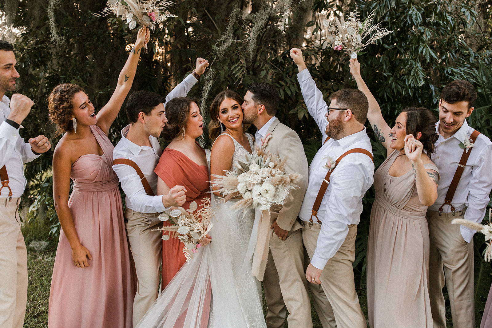 Real Bride and Groom Kissing at Outdoor Wedding with Bridal Party Cheering on the Side