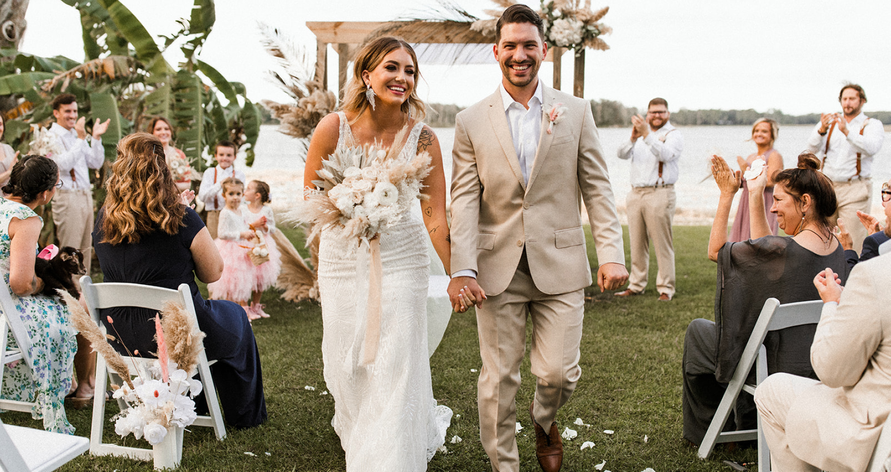 Real Bride Kaley Wearing Maggie Sottero Wedding Dress and Walking Down the Aisle with Groom at Lakeside Wedding