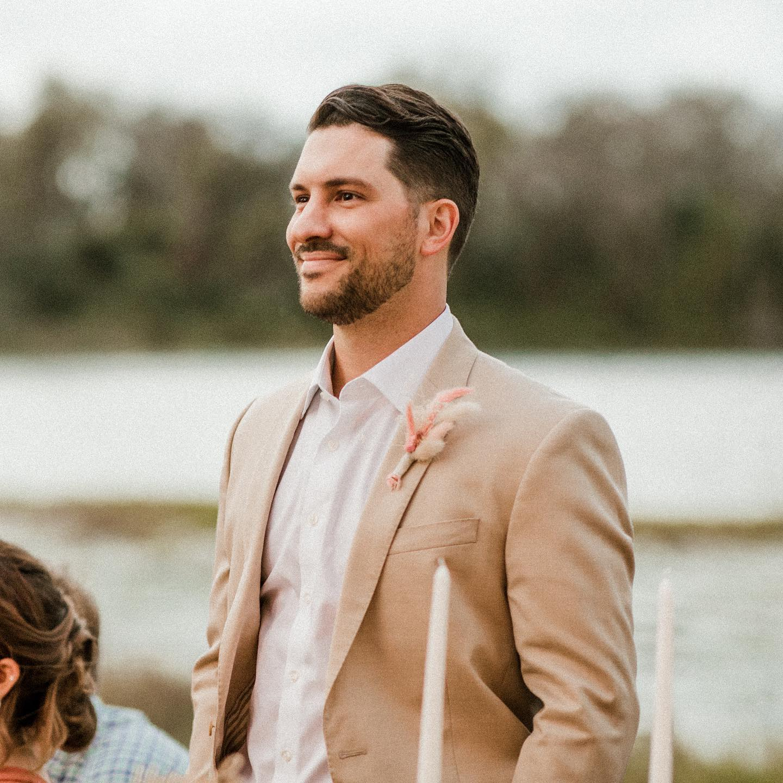 Groom Wearing Tan Suit at Lakeside Wedding