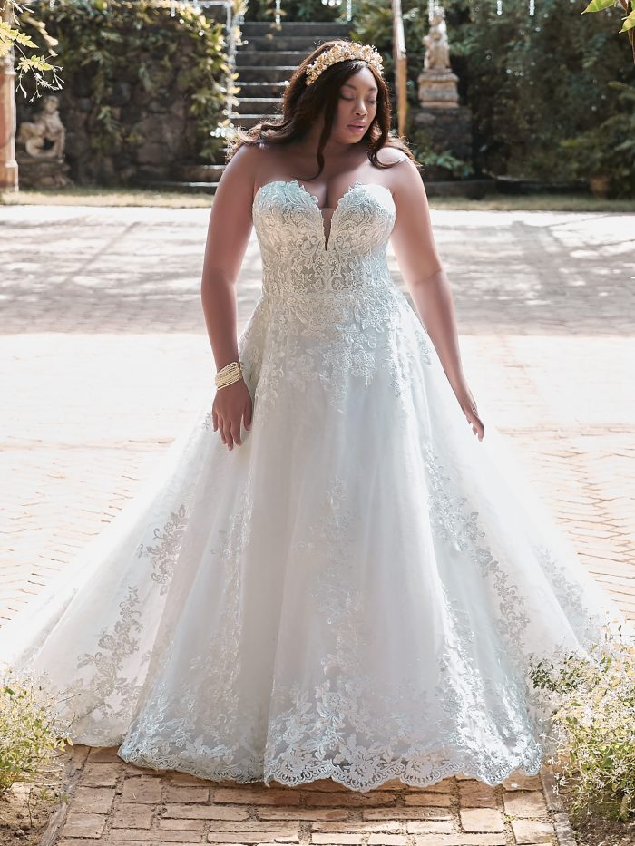 Plus Size Model Wearing Curvy Strapless Lace Ball Gown Wedding Dress Called Tennyson by Maggie Sottero