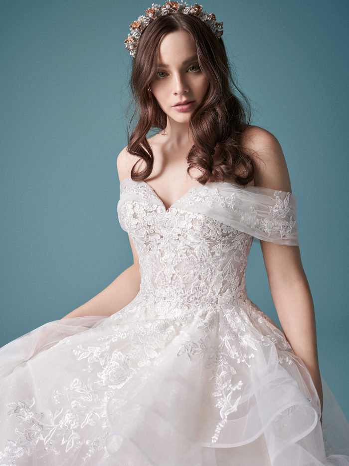 Model Wearing Off-the-Shoulder Blush Ball Gown Wedding Dress with Horsehair Hem Called Zariah by Maggie Sottero