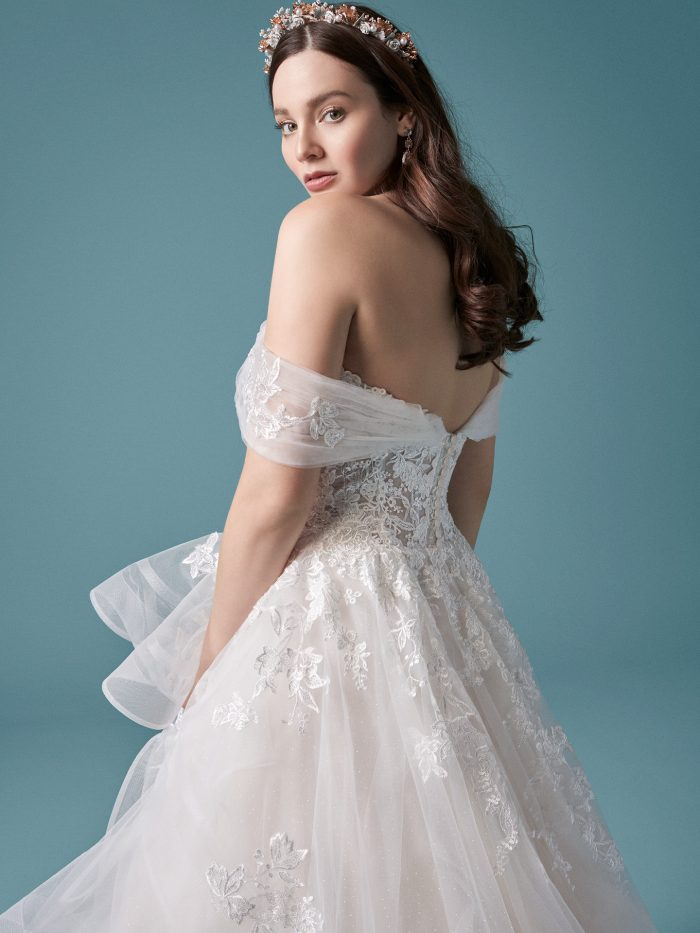 Model Wearing Off-the-Shoulder Ball Gown Wedding Dress with Horsehair Hem Called Zariah by Maggie Sottero