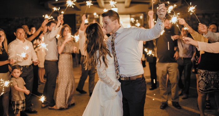Groom Holding Sparkler and Kissing Bride Wearing Lace Wedding Dress by Maggie Sottero