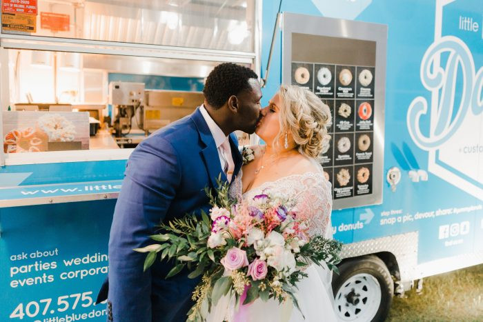 Bride and Groom Kissing in Front of Homemade Donut Truck at Spring Wedding