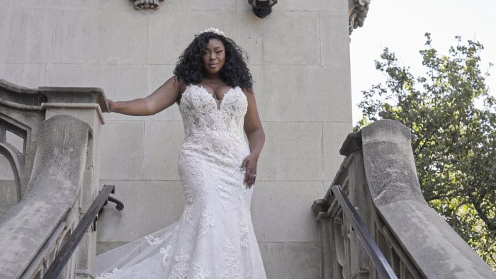 Black Plus Size Model Wearing Curvy Fit-and-Flare Wedding Dress Called Farrah by Maggie Sottero