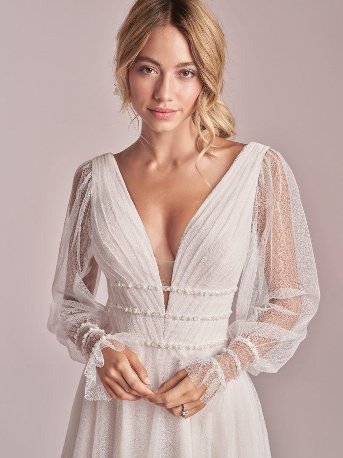 Model Wearing Sheer Bishop Sleeve A-line Wedding Gown Called Joanne by Rebecca Ingram