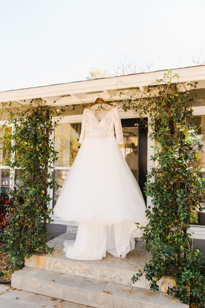 Lace Ball Gown Wedding Dress Called Mallory Dawn by Maggie Sottero Hanging from Doorway Outside