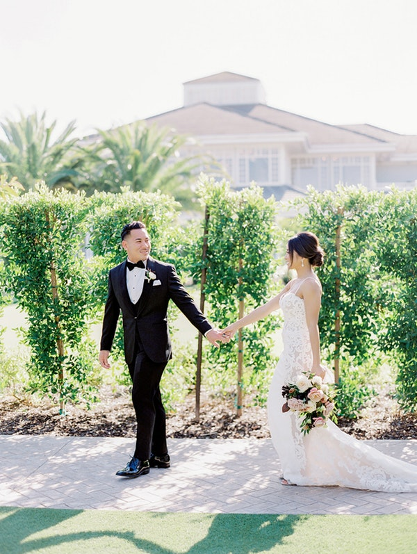 Groom Holding Hands with Bride Wearing Soft Updo