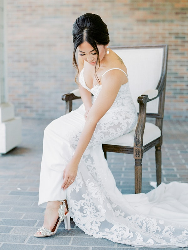 Bride Putting on Shoe and Wearing Soft Updo