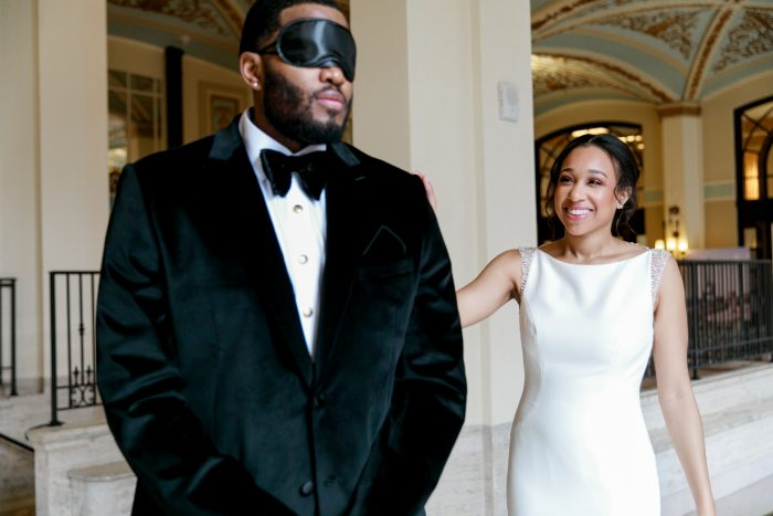 Groom Wearing Blindfold and Bride Walking Up Behind Him During First Look