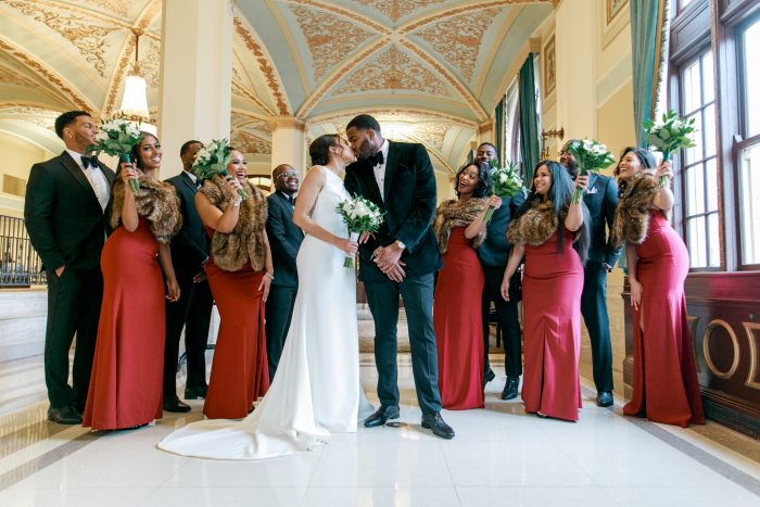 Wedding Party Celebrating Behind Real Bride and Groom Kissing in Fancy Venue