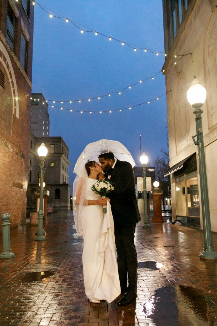 Real Bride and Groom Under Umbrella in a Historic Street at Ritzy Wedding