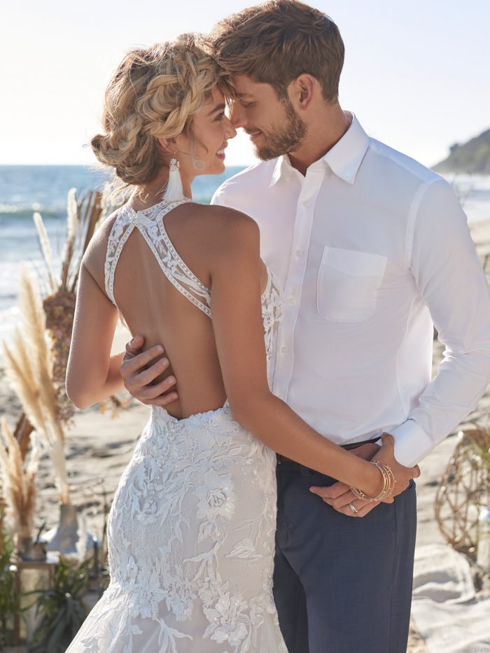 Groom with Bride on Beach Wearing Affordable Sexy Backless Mermaid Wedding Gown Called Elizabetta by Rebecca Ingram