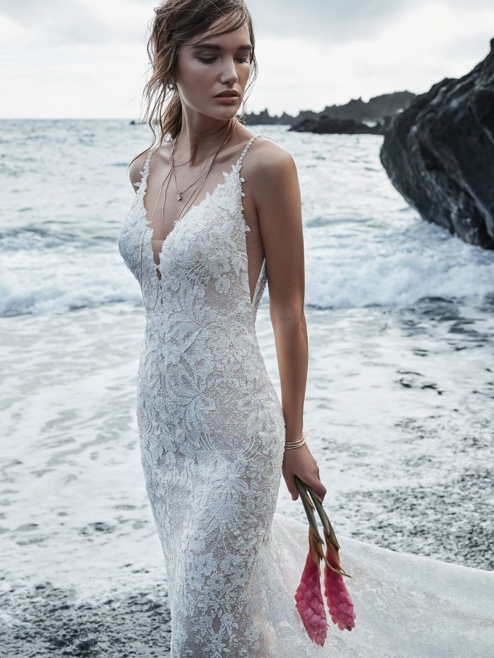 Model on Beach Wearing Lace Sheath Wedding Dress with Long Train Called Canterbury Marie by Sottero and Midgley