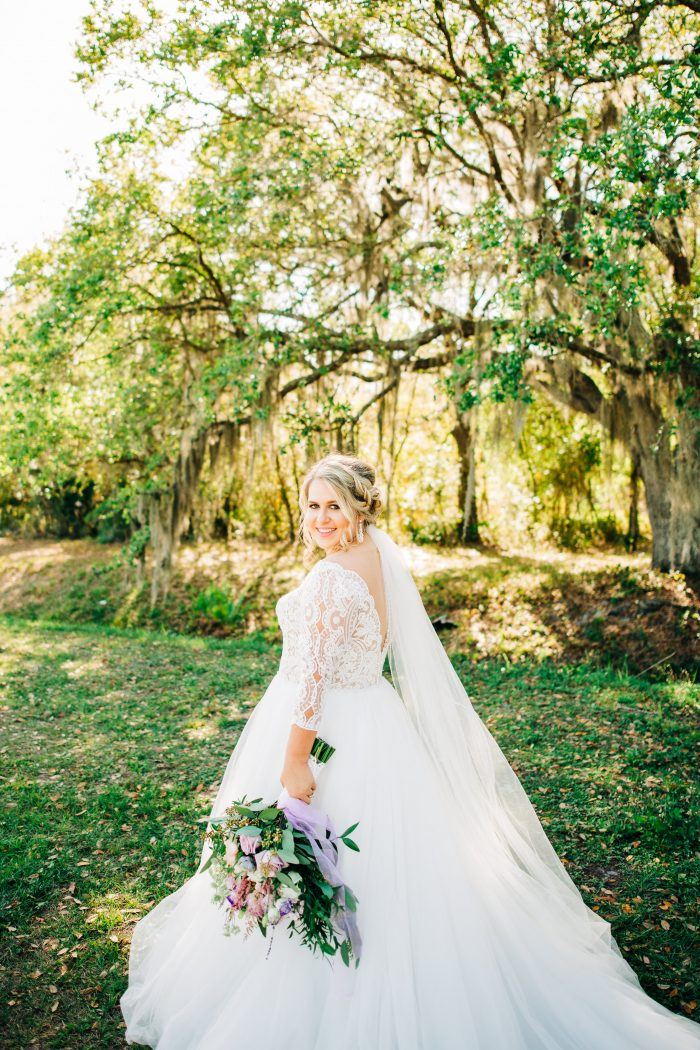 Plus Size Bride on Wedding Day Holding Bouquet and Wearing Scallop Lace Off the Shoulder Wedding Dress Called Mallory Dawn by Maggie Sottero