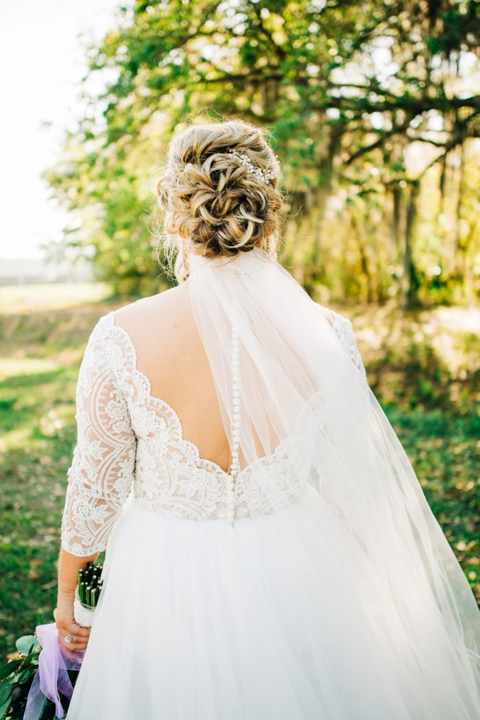 Plus Size Bride From Back Wearing Scallop Lace Off the Shoulder Wedding Dress Called Mallory Dawn by Maggie Sottero and Classic Chignon with Veil