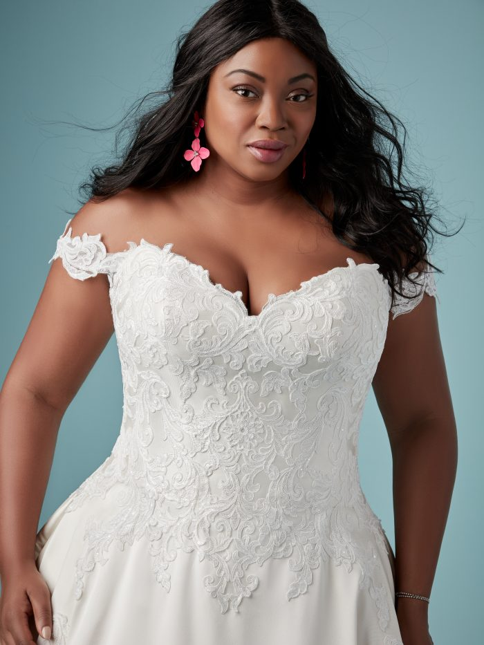 Curvy Black Bride Wearing Off-the-Shoulder Satin Ball Gown Wedding Dress Called Sheridan by Maggie Sottero with Pockets