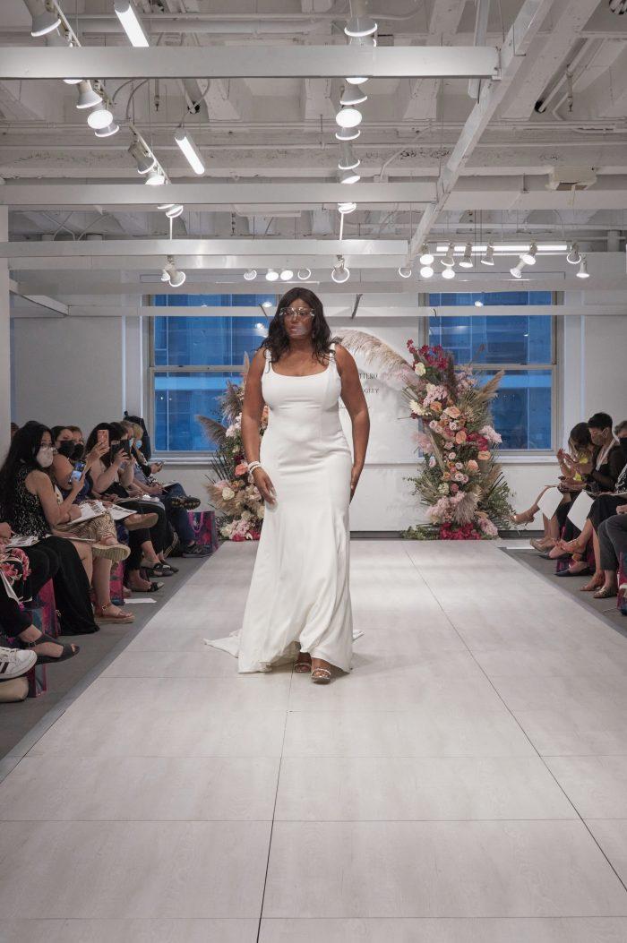 Model Walking Down the Runway at Chicago Bridal Market Wearing Plus Size Sheath Wedding Dress Called Emerald by Rebecca Ingram