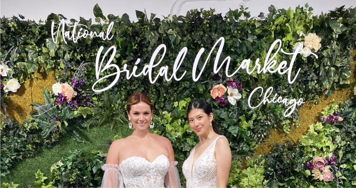 Two Models in Maggie Sottero Wedding Dresses Standing in front of Chicago Bridal Market Sign