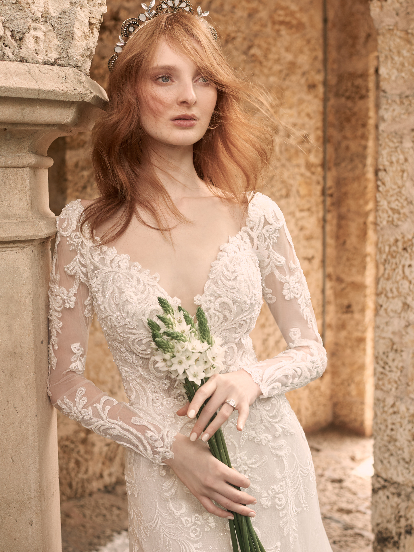 Model Holding Bouquet and Wearing Illusion Lace Sleeve Wedding Gown Called Johanna by Maggie Sottero