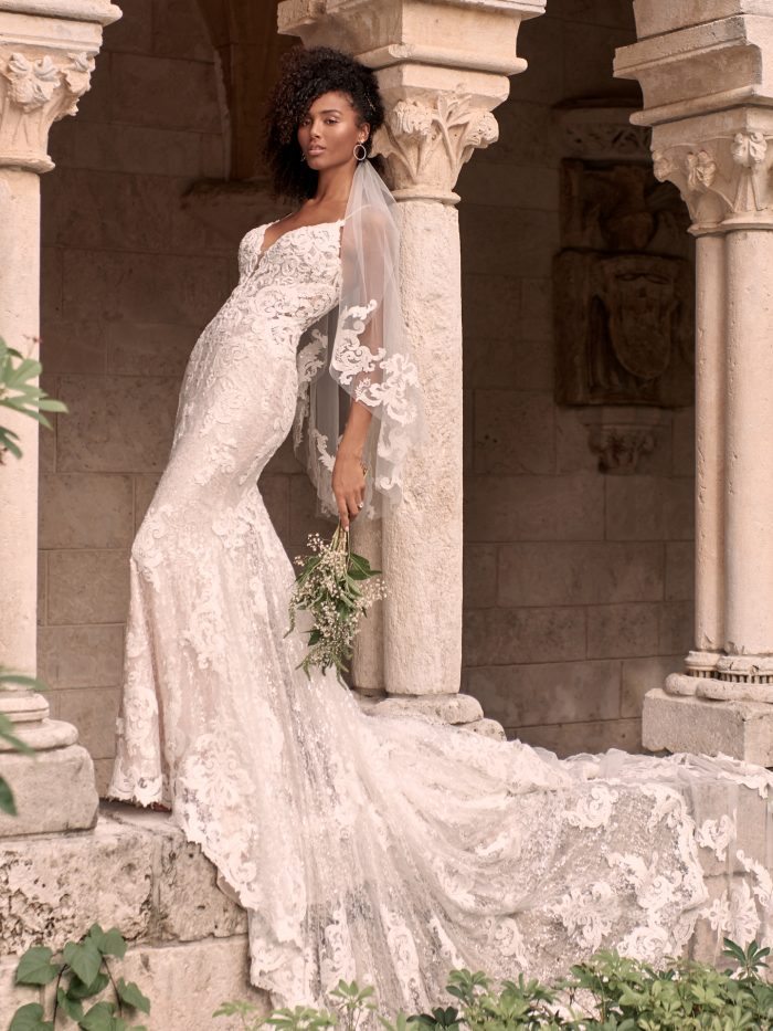 Black Model Wearing Sparkly Lace Sheath Bridal Gown with Extended Train Called Tuscany Royale by Maggie Sottero
