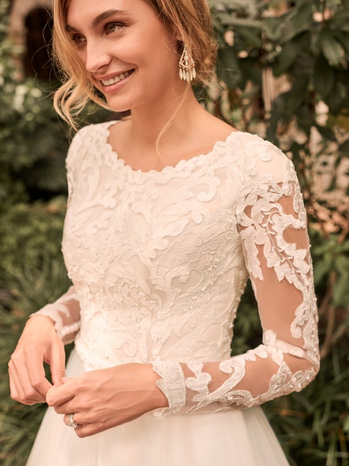Model Wearing Modest Illusion Lace Sleeve Ball Gown Wedding Dress Called Carrie Leigh by Rebecca Ingram