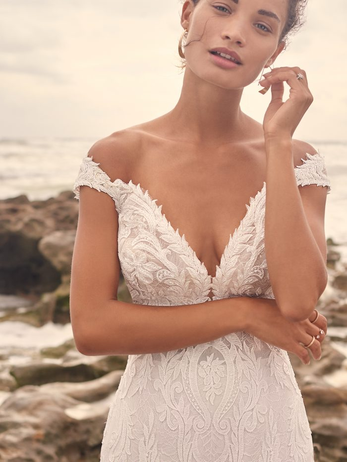 Model on Beach Wearing Cap-Sleeve Lace Mermaid Wedding Dress Called Joss by Sottero and Midgley