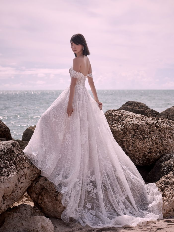 Model on Beach Wearing Fairytale Off-the-Shoulder Bridal Gown Called Parker by Sottero and Midgley