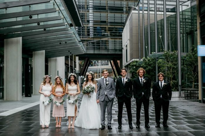 Boho Bride and Groom Standing with Their Groomsmen and Bridesmaids at Real Wedding