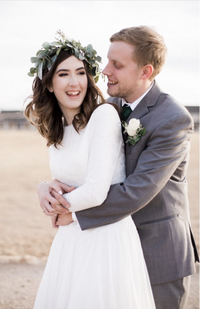 Groom Laughing with Real Bride Wearing Modest Weddinng Dress and Whimsical Flower Crown During Wedding Shoot