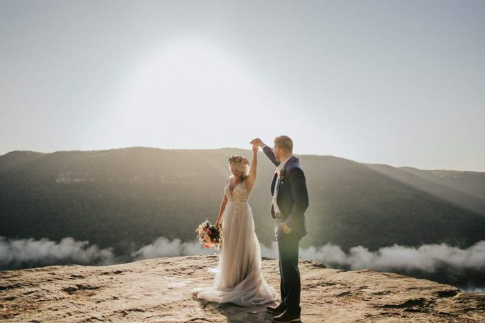 Groom with Real Bride Wearing Flower Crown and Floral Wedding Dress Called Raelynn by Rebecca Ingram
