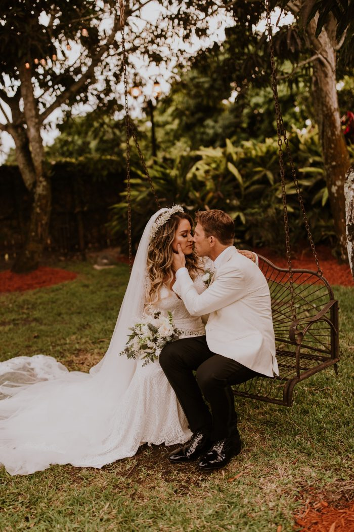 Groom on Bench Kissing Real Bride Wearing Boho Wedding Dress Called Antonia by Maggie Sottero