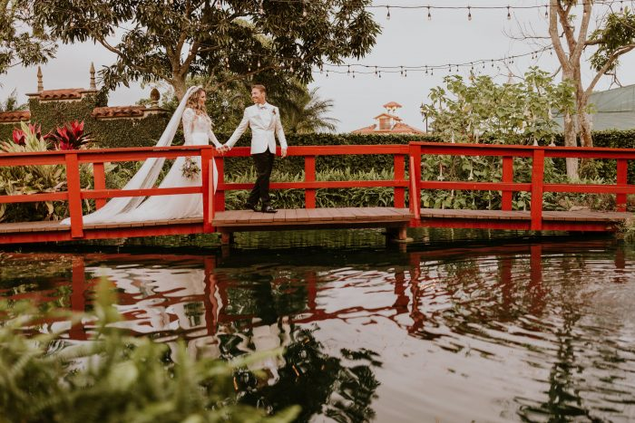 Groom on Red Bridge with Real Bride Wearing Boho Flower Crown and Boho Wedding Dress by Maggie Sottero