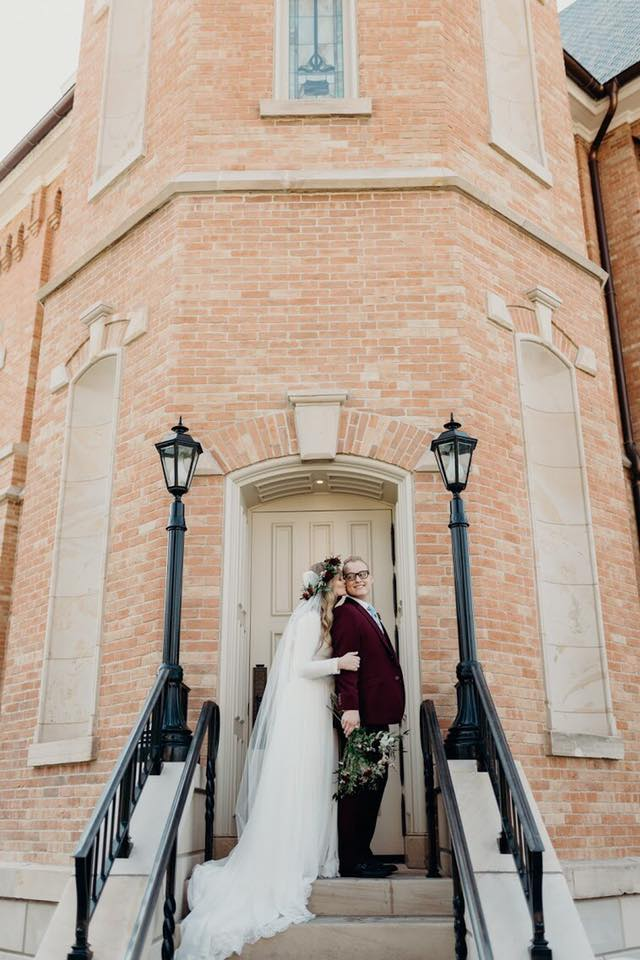 Bride Hugging Groom at Provo LDS Temple and Wearing Modest Lace Wedding Dress by Maggie Sottero