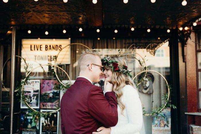 Groom Kissing Bride Wearing Flower Crown at Moody Punk Rock Wedding